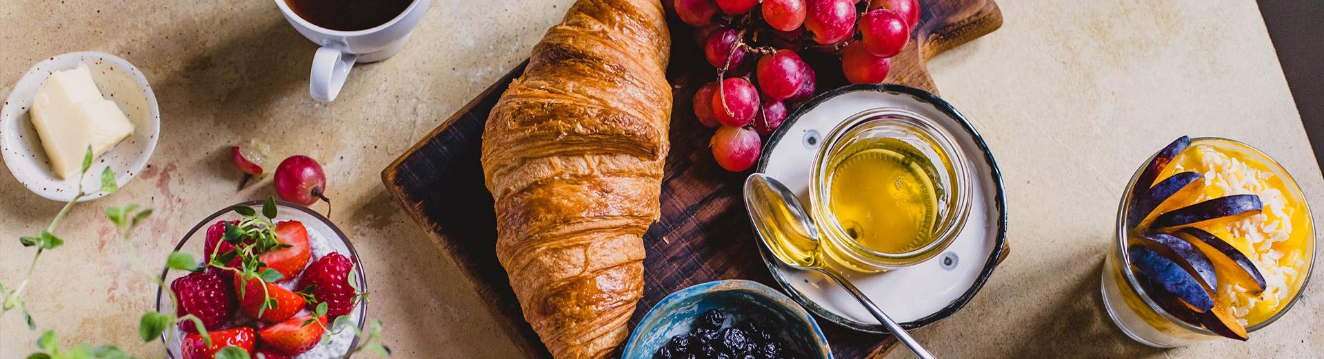 Frühstücksbuffett mit Hörnchen und frischem Obst